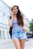 Γυναίκα που χρησιμοποιεί το κινητό τηλέφωνο στην οδό πόλεων Στοκ Εικόνες