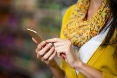 Γυναίκα που χρησιμοποιεί το κινητό τηλέφωνο στο τμήμα παντοπωλείων στοκ φωτογραφίες με δικαίωμα ελεύθερης χρήσης