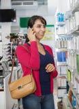 Γυναίκα που χρησιμοποιεί το κινητό τηλέφωνο στο φαρμακείο στοκ φωτογραφία με δικαίωμα ελεύθερης χρήσης