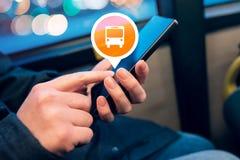 Γυναίκα που χρησιμοποιεί το κινητό τηλέφωνο app στο ηλεκτρονικό εισιτήριο λεωφορείων αγορών Στοκ Εικόνες