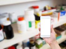 Γυναίκα που χρησιμοποιεί το κινητό smartphone στο φαρμακείο στοκ εικόνες με δικαίωμα ελεύθερης χρήσης