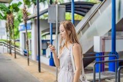 Γυναίκα που χρησιμοποιεί το τηλέφωνο app για το γύρο ταξί που χαιρετά την υπηρεσία ή που χρησιμοποιεί το τηλέφωνο app για να βρεί στοκ εικόνα με δικαίωμα ελεύθερης χρήσης