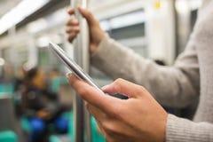 Γυναίκα που χρησιμοποιεί το τηλέφωνο κυττάρων της στον υπόγειο Στοκ Εικόνες