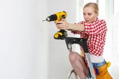 Γυναίκα που χρησιμοποιεί το τρυπάνι στη σκάλα στοκ φωτογραφίες