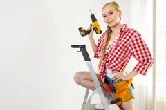 Γυναίκα που χρησιμοποιεί το τρυπάνι στη σκάλα στοκ φωτογραφία με δικαίωμα ελεύθερης χρήσης
