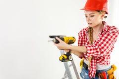 Γυναίκα που χρησιμοποιεί το τρυπάνι στη σκάλα στοκ εικόνα με δικαίωμα ελεύθερης χρήσης
