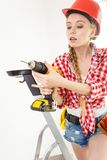 Γυναίκα που χρησιμοποιεί το τρυπάνι στη σκάλα Στοκ Εικόνα