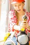 Γυναίκα που χρησιμοποιεί το τρυπάνι στο παράθυρο στοκ φωτογραφίες με δικαίωμα ελεύθερης χρήσης
