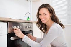 Γυναίκα που χρησιμοποιεί το φούρνο Στοκ εικόνα με δικαίωμα ελεύθερης χρήσης