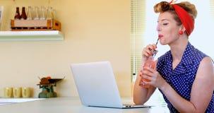 Γυναίκα που χρησιμοποιεί το lap-top ενώ έχοντας το χυμό 4k απόθεμα βίντεο