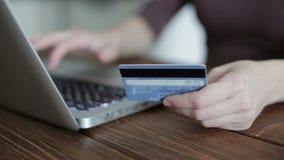 Γυναίκα που χρησιμοποιεί το lap-top και την πιστωτική κάρτα λαβής απόθεμα βίντεο