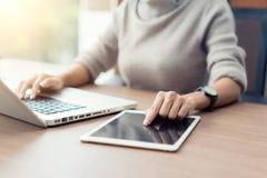 Γυναίκα που χρησιμοποιεί το lap-top και την ψηφιακή ταμπλέτα κατά τη διάρκεια της εργασίας στην αρχή, Στοκ Εικόνες