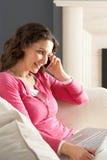 Γυναίκα που χρησιμοποιεί το lap-top στον καναπέ στο σπίτι στο τηλέφωνο στοκ φωτογραφία με δικαίωμα ελεύθερης χρήσης