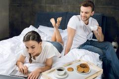 Γυναίκα που χρησιμοποιεί το lap-top στο κρεβάτι ενώ καφές κατανάλωσης ανδρών στοκ φωτογραφίες