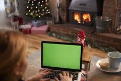 Γυναίκα που χρησιμοποιεί το lap-top στο δωμάτιο που διακοσμείται για τα Χριστούγεννα Στοκ εικόνες με δικαίωμα ελεύθερης χρήσης