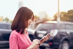 Γυναίκα που χρησιμοποιεί το smartphone για την εφαρμογή στο υπόβαθρο θαμπάδων αυτοκινήτων στοκ φωτογραφία με δικαίωμα ελεύθερης χρήσης