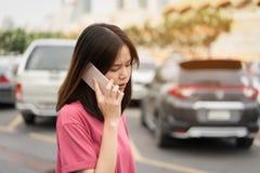 Γυναίκα που χρησιμοποιεί το smartphone για την εφαρμογή στο υπόβαθρο θαμπάδων αυτοκινήτων στοκ εικόνες