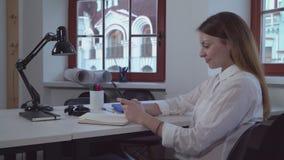 Γυναίκα που χρησιμοποιεί το smartphone η θέση εργασίας απόθεμα βίντεο