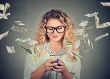Γυναίκα που χρησιμοποιεί το smartphone με τους λογαριασμούς δολαρίων που πετούν μακρυά από την οθόνη Στοκ φωτογραφίες με δικαίωμα ελεύθερης χρήσης