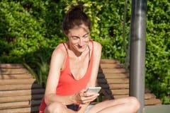 Γυναίκα που χρησιμοποιεί το smartphone στην καρέκλα γεφυρών σαλονιών Στοκ φωτογραφίες με δικαίωμα ελεύθερης χρήσης