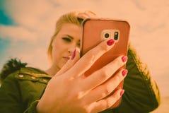 Γυναίκα που χρησιμοποιεί το smartphone της έξω, ηλιόλουστη ημέρα Στοκ Φωτογραφίες