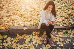 Γυναίκα που χρησιμοποιεί το smartphone το φθινόπωρο Κορίτσι φθινοπώρου που έχει την έξυπνη τηλεφωνική συνομιλία στο φύλλωμα φλογώ Στοκ Φωτογραφίες