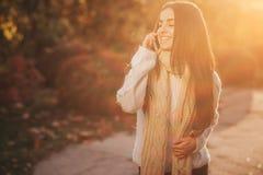 Γυναίκα που χρησιμοποιεί το smartphone το φθινόπωρο Κορίτσι φθινοπώρου που έχει την έξυπνη τηλεφωνική συνομιλία στο φύλλωμα φλογώ Στοκ Εικόνα