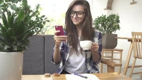 Γυναίκα που χρησιμοποιεί app στο smartphone στον καφέ και το γέλιο κατανάλωσης καφέδων Στοκ φωτογραφία με δικαίωμα ελεύθερης χρήσης