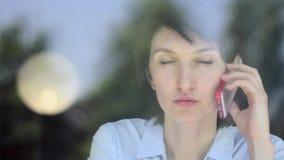 Γυναίκα που χρησιμοποιεί app στο smartphone στον καφέ κατανάλωσης καφέδων που χαμογελά και που στο κινητό τηλέφωνο Όμορφες πολυπο απόθεμα βίντεο