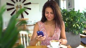 Γυναίκα που χρησιμοποιεί app στο smartphone στον καφέ κατανάλωσης καφέδων Στοκ φωτογραφίες με δικαίωμα ελεύθερης χρήσης
