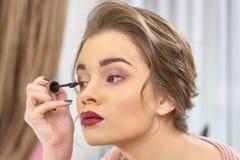Γυναίκα που χρησιμοποιεί eyelash τη βούρτσα στοκ φωτογραφίες