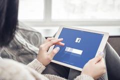 Γυναίκα που χρησιμοποιεί Facebook app στην ολοκαίνουργια Apple iPad υπέρ Στοκ φωτογραφία με δικαίωμα ελεύθερης χρήσης