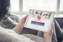 Γυναίκα που χρησιμοποιεί Pinterest app στην ολοκαίνουργια Apple iPad υπέρ Στοκ Εικόνες