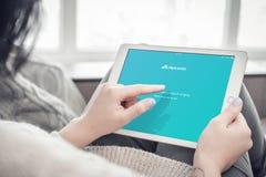 Γυναίκα που χρησιμοποιεί Skyscanner apps στην ολοκαίνουργια Apple iPad υπέρ Στοκ Φωτογραφίες