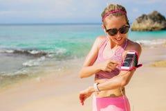 Γυναίκα που χρησιμοποιεί workout την καταδίωξη app στο τηλέφωνο Στοκ εικόνα με δικαίωμα ελεύθερης χρήσης