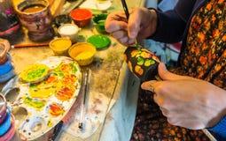 Γυναίκα που χρωματίζει την παραδοσιακή ρωσική ξύλινη να τοποθετηθεί κούκλα στοκ εικόνες με δικαίωμα ελεύθερης χρήσης