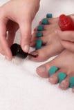 Γυναίκα που χρωματίζει toenails της με το κόκκινο βερνίκι Στοκ Εικόνες