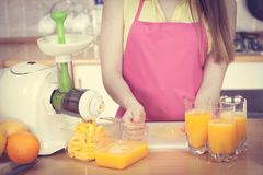 Γυναίκα που χύνει το ποτό χυμού από πορτοκάλι στο γυαλί Στοκ Εικόνες