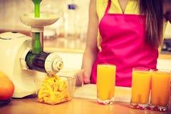Γυναίκα που χύνει το ποτό χυμού από πορτοκάλι στο γυαλί Στοκ Φωτογραφίες