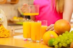 Γυναίκα που χύνει το ποτό χυμού από πορτοκάλι στο γυαλί Στοκ φωτογραφίες με δικαίωμα ελεύθερης χρήσης
