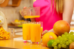 Γυναίκα που χύνει το ποτό χυμού από πορτοκάλι στο γυαλί Στοκ εικόνες με δικαίωμα ελεύθερης χρήσης