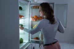 Γυναίκα που ψάχνει για τα τρόφιμα στο ψυγείο στοκ φωτογραφία με δικαίωμα ελεύθερης χρήσης