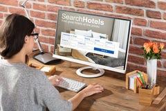 Γυναίκα που ψάχνει τα ξενοδοχεία on-line στοκ εικόνες