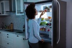 Γυναίκα που ψάχνει τα τρόφιμα στο ψυγείο στοκ φωτογραφία με δικαίωμα ελεύθερης χρήσης