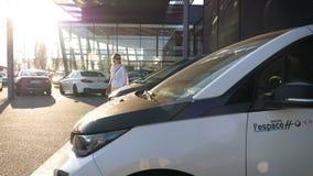 Γυναίκα που ψωνίζει για την υπαίθρια αίθουσα εκθέσεως αυτοκινήτων της BMW i3 i32 απόθεμα βίντεο