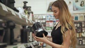 Γυναίκα που ψωνίζει για τις συσκευές κουζινών απόθεμα βίντεο