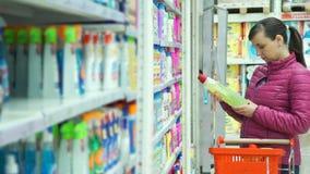 Γυναίκα που ψωνίζει και που διαβάζει τις πληροφορίες προϊόντων φιλμ μικρού μήκους