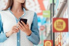 Γυναίκα που ψωνίζει και που χρησιμοποιεί το τηλέφωνό της στοκ φωτογραφία με δικαίωμα ελεύθερης χρήσης