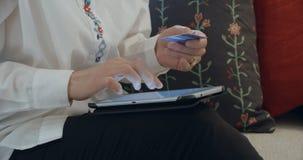 Γυναίκα που ψωνίζει με το PC ταμπλετών και την πιστωτική κάρτα απόθεμα βίντεο