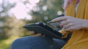 Γυναίκα που ψωνίζει χρησιμοποιώντας το PC ταμπλετών και την πιστωτική κάρτα απόθεμα βίντεο